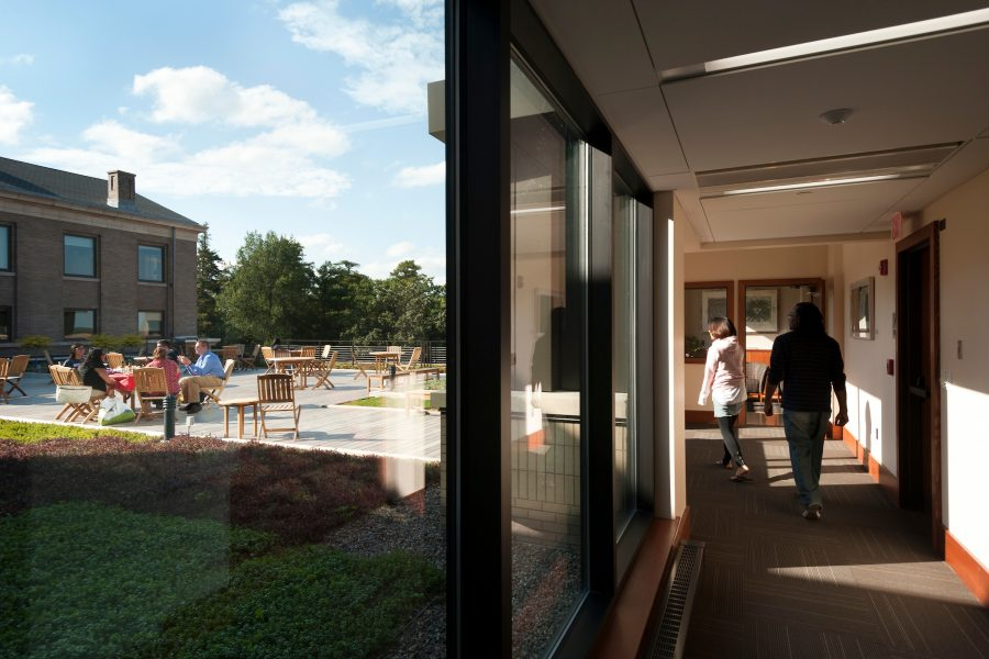 group meeting on rooftop terrace and people walking in hallway